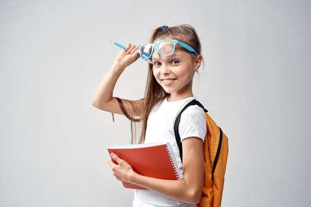niño, niña corrige gafas, colegiala. Foto de archivo