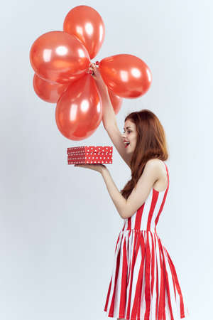 woman holds a red box and balls, joy, holiday. Stock Photo