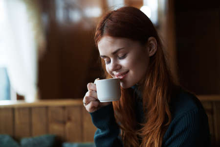 woman in a sweater drinking coffee in a cafe, portrait.