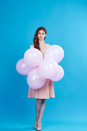 woman in shoes and in dress holds balloons.