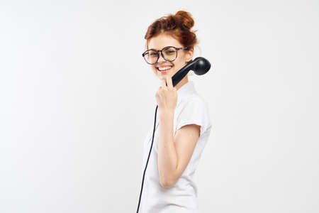 a woman in glasses with a bundle on her head is holding a landline phone, a smile.