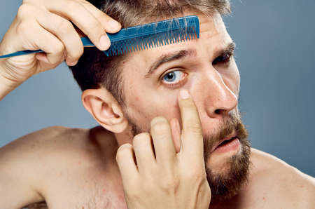 man combs his eyebrows, portrait, close-up.
