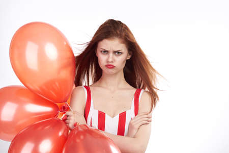 woman in red holds balloons on white isolated background. Stock Photo