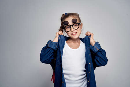 notebook: A little girl with glasses adjusts her shirt and backpack. Stock Photo