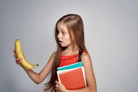little girl in a vest holds a banana.