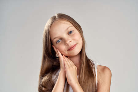 little girl with long hair on a light gray background, portrait.