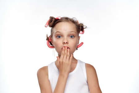 little girl with hair curlers on hair on white isolated background covered her face with face, surprise, emotion.