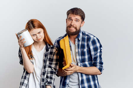 a man with a molar bath, a woman holding a paint jar on a light background, repairing an apartment, building materials.