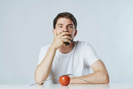 man thinks a vegetarian is sitting at a table with a tomato on a light background, the right food. Stock Photo