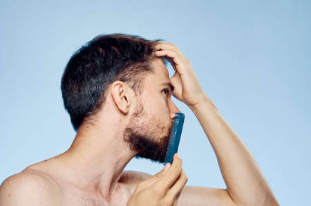 man combing his beard on a light blue background.
