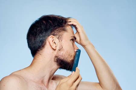 metrosexual: man combing his beard on a light blue background.