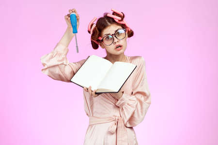 girl in curlers on a pink background poking a screwdriver in a notebook. Stock Photo