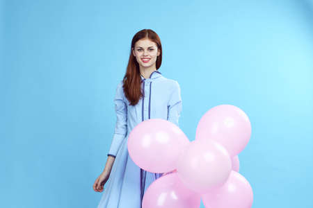 happy girl in a blue dress with balloons and on a light blue background.