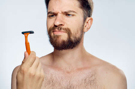 the man looks doubtfully at the razor in his hand.