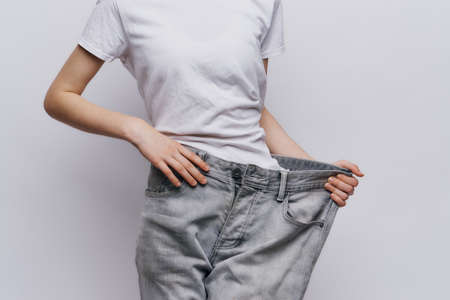 a woman in a white T-shirt and pants that are too big for her. Stock Photo