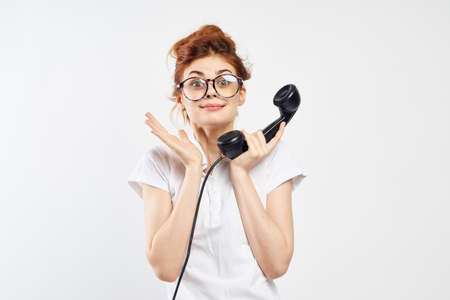 red-haired girl in a white T-shirt and a telephone receiver in her hand on a light background.