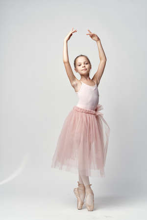 ballerina tights: little ballerina in a light bundle and pointe poses with her arms raised. Stock Photo