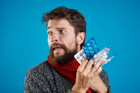 A bearded man in dark clothes with an armful of pills in his hands.