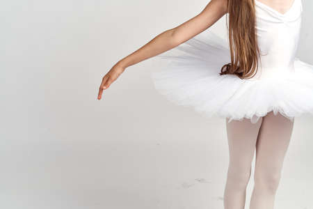 A small ballerina in a pack and an outstretched pen on a gray background.