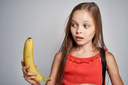 little girl in red dress looks very surprised at yellow banana. Zdjęcie Seryjne - 88486871