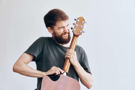 bearded man tries to master the guitar with all his might. Stock Photo