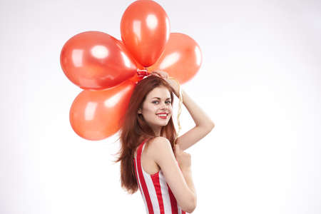 beautiful woman holds balloons in a red dress on a white background.