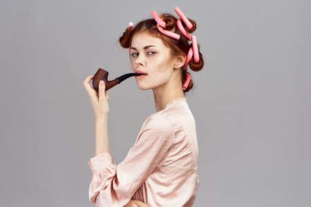 Huisvrouw met krulspelden op haar hoofd roken van een pijp op een grijze achtergrond.