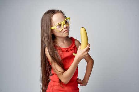 メガネ少女の女子高生は、灰色の背景にバナナに見えます。