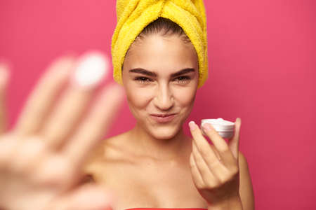 young girl with a yellow towel on her head holds a face cream. Banco de Imagens