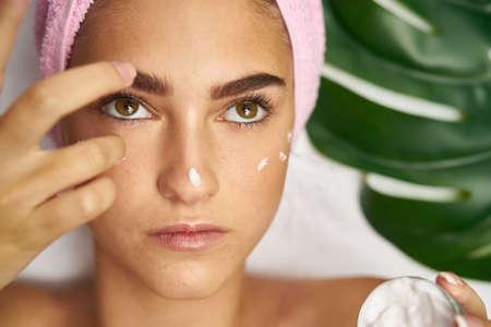 woman bath: woman on spa treatment with cream on face.