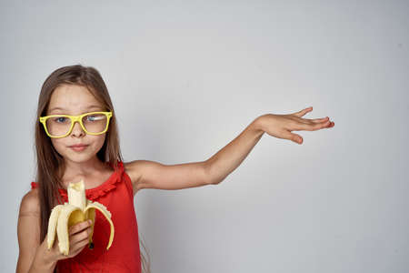 Little girl eating a banana and pointing.