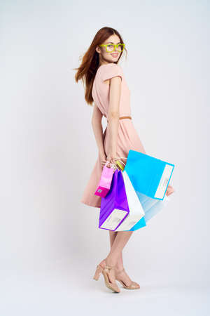 consumerism: girl in a light dress with shopping bags.