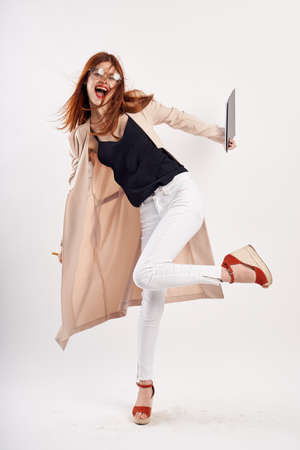 the girl fools around with the tablets in her cream coat. Stock Photo