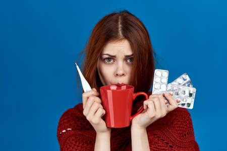 a girl with red hair, a mug and a sweater is holding a lot of pills and a thermometer on a blue background.