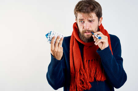 man with a mountain of tablets and a thermometer in warm clothes. Stock Photo