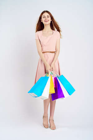 joyful girl in a cream dress with purchases on a light background.