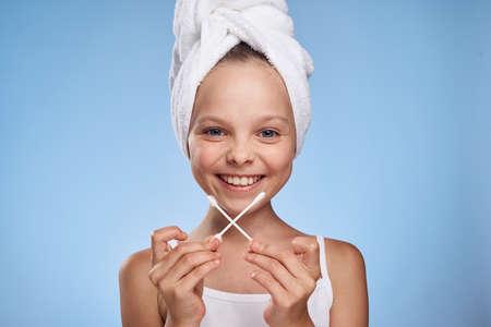niña en toalla con capullos de algodón sonriendo.