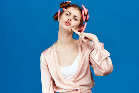 girl in curlers on a blue background.