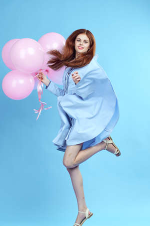 woman with pink balloons on a blue background in a fluttering dress.