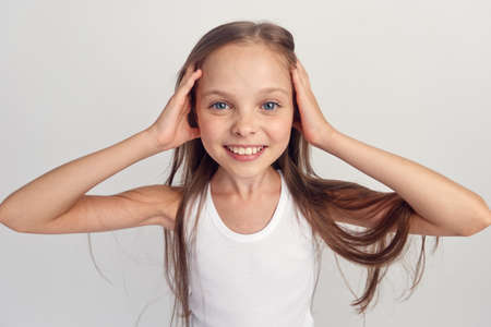 the little girl smiles and clings to her head. Stock Photo