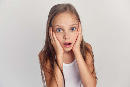 little girl on a gray background surprised.