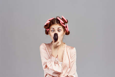 a girl in curlers covers her face on a gray background. Stock Photo