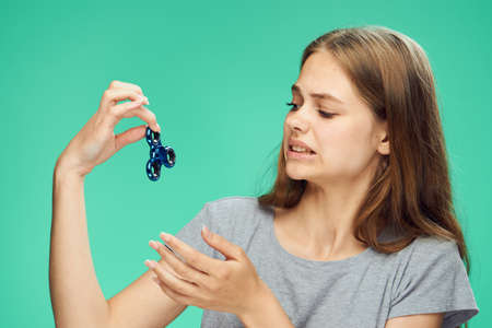 the girl does not really like the spinner on the green background. Stock Photo