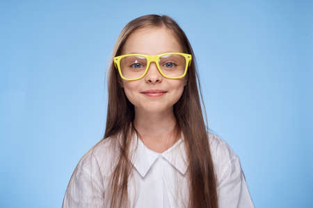 a little girl in yellow glasses sincerely smiles.