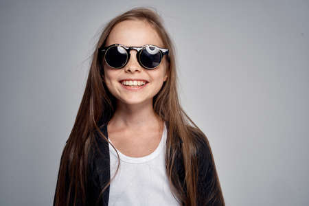 young girl in black glasses sincerely smiling. Stock Photo