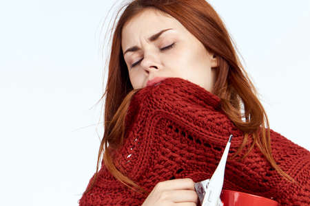 sick woman covered her face with a red scarf, close-up. Stock Photo