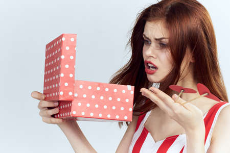 Red-haired girl peeps into the gift box and is not very happy. Stock Photo