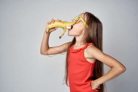 little girl in a red dress on a gray background eating a banana.