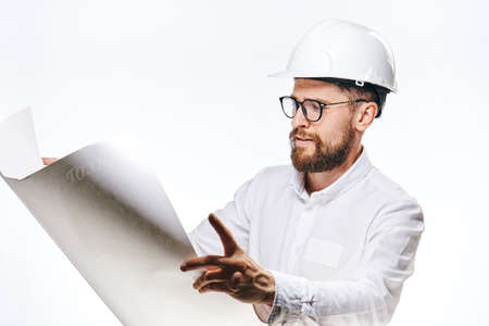 male engineer in white examining plan.