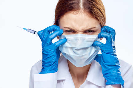 woman in a medical mask holds a syringe, portrait, emotions.